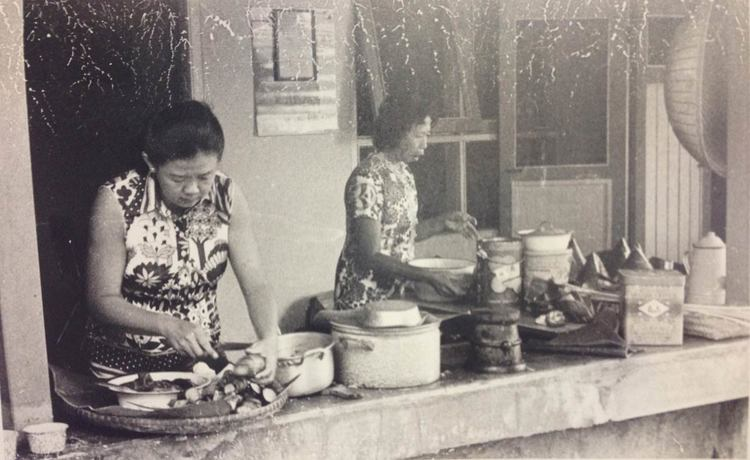 Photograph from May-Li's parents' collection. Food is being prepared semi-outdoors, and banana leaves provide a natural wrapping or plate.
